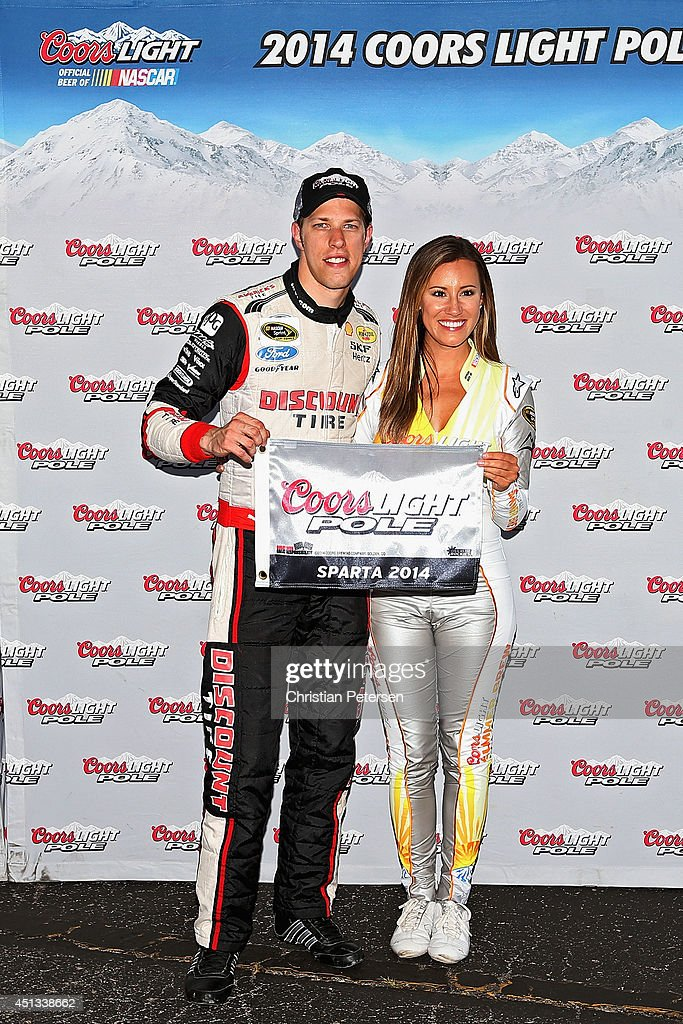 Brad Keselowski, driver of the #2 Miller Lite Ford, left, poses with Miss Coors Light Rachel Rupert and the Coors Light Pole Award after qualifying for the pole for the NASCAR Sprint Cup Series Quaker State 400 presented by Advance Auto Parts at Kentucky Speedway on June 27, 2014 in Sparta, Kentucky.