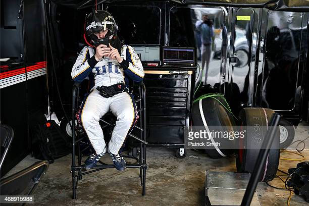 Brad Keselowski driver of the Miller Lite Ford looks at his cell phone as crews work on his car in the garage area during the NASCAR Sprint Cup...