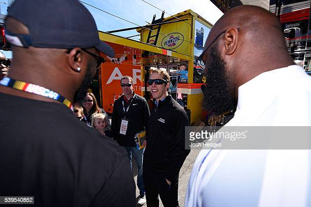 Brad Keselowski, driver of the Miller Lite Ford, meets with NFL players A'Shawn Robinson and Antwione Williams of the Detroit Lions before the NASCAR...