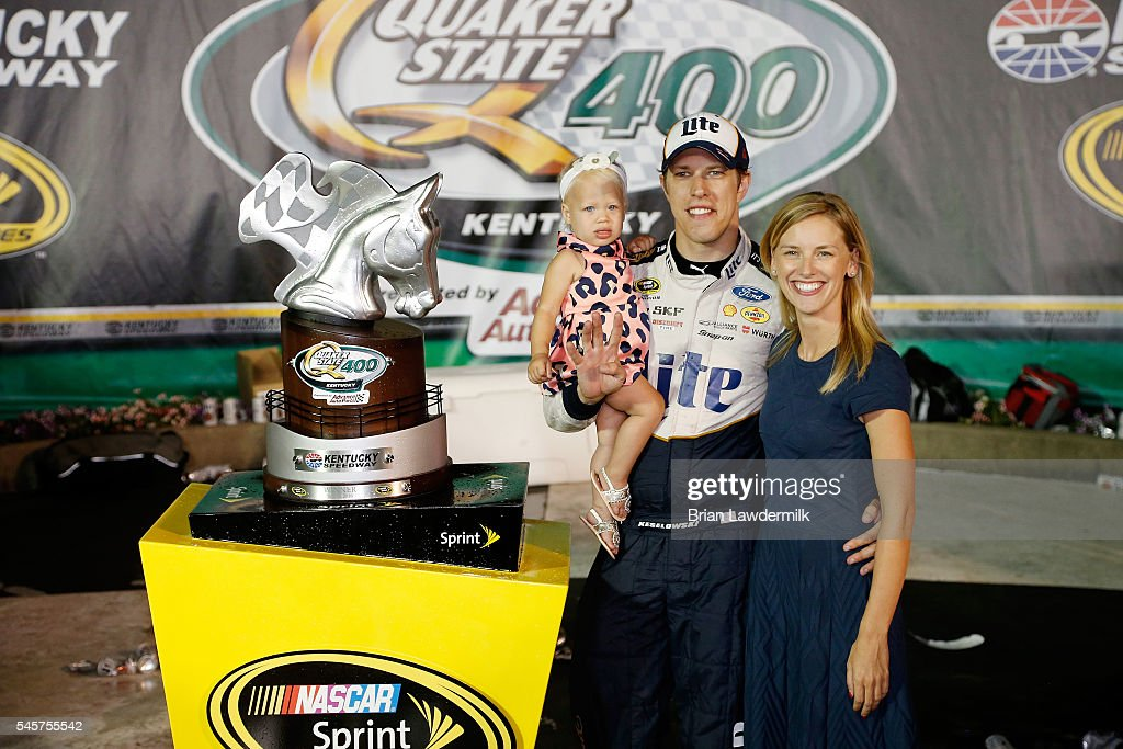 Brad Keselowski, driver of the #2 Miller Lite Ford, poses in Victory Lane with his girlfriend, Paige White, and daughter, Scarlett, after winning the NASCAR Sprint Cup Series Quaker State 400 at Kentucky Speedway on July 9, 2016 in Sparta, Kentucky.