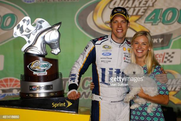 Brad Keselowski driver of the Miller Lite Ford poses with girlfriend Paige White in with the trophy after winning the NASCAR Sprint Cup Series Quaker...
