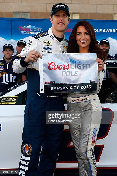 Brad Keselowski driver of the Miller Lite Ford poses with Miss Coors Light Amanda Mertz and the Coors Light Pole award after qualifying for pole...