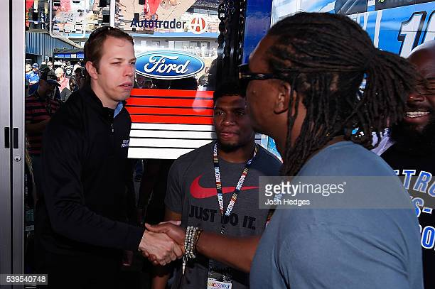 Brad Keselowski driver of the Miller Lite Ford shakes hands with NFL player Ezekiel 'Ziggy' Ansah of the Detroit Lions before the NASCAR Sprint Cup...