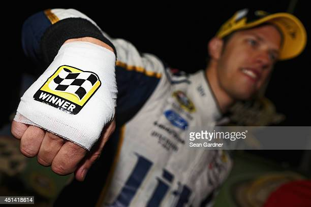 Brad Keselowski driver of the Miller Lite Ford shows his bandaged hand after cutting himself while celebrating with champagne in Victory Lane after...