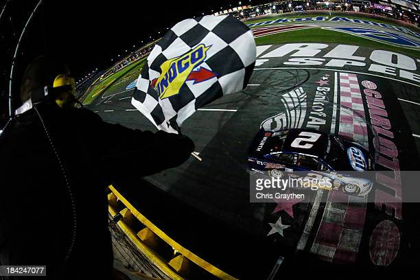 Brad Keselowski driver of the Miller Lite Ford takes the checkered flag as he crosses the finish line to win the NASCAR Sprint Cup Series Bank of...