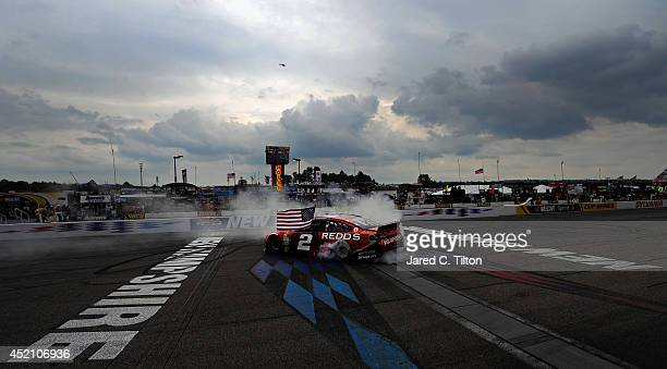 Brad Keselowski driver of the Redds Ford celebrates with a burnout after winning the NASCAR Sprint Cup Series Camping World RV Sales 301 at New...