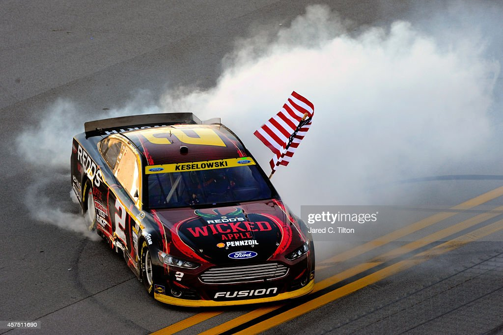 Brad Keselowski, driver of the #2 Redd's Wicked Apple Ale Ford, celebrates with a burnout after winning the NASCAR Sprint Cup Series GEICO 500 at Talladega Superspeedway on October 19, 2014 in Talladega, Alabama.