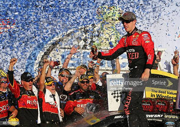 Brad Keselowski driver of the Redd's Wicked Apple Ale Ford celebrates in victory lane after winning the NASCAR Sprint Cup Series GEICO 500 at...