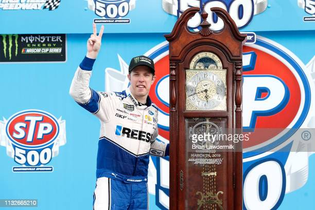 Brad Keselowski driver of the Reese/Draw Tite Ford poses with the trophy in Victory Lane after winning the Monster Energy NASCAR Cup Series STP 500...