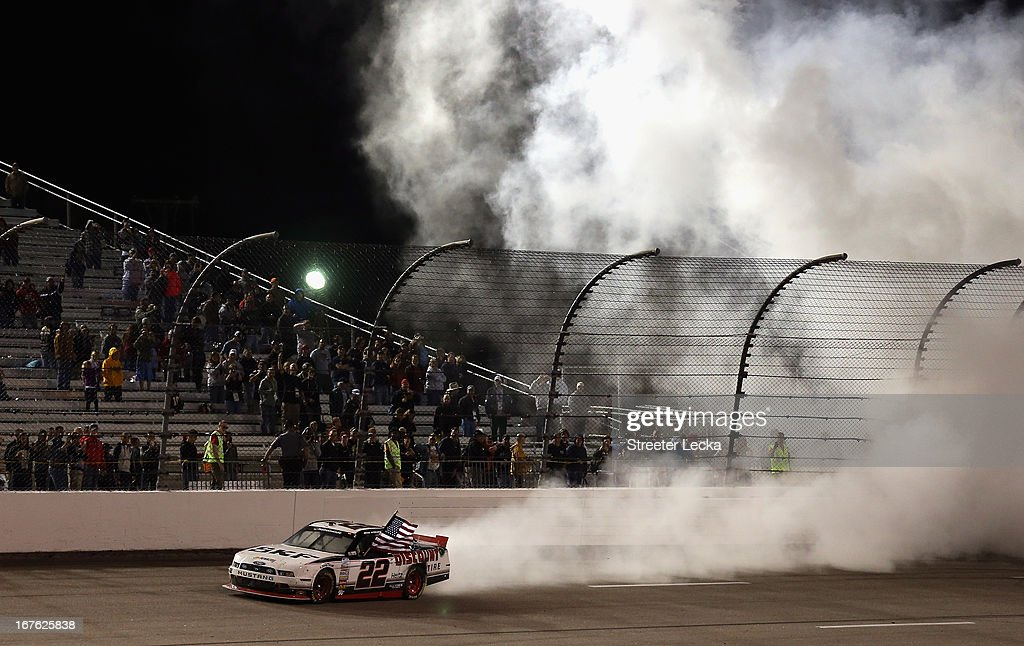 Brad Keselowski, driver of the #22 SKF / Discount Tire Ford, performs a burn out to celebrate after winning the NASCAR Nationwide Series ToyotaCare 250 at Richmond International Raceway on April 26, 2013 in Richmond, Virginia.