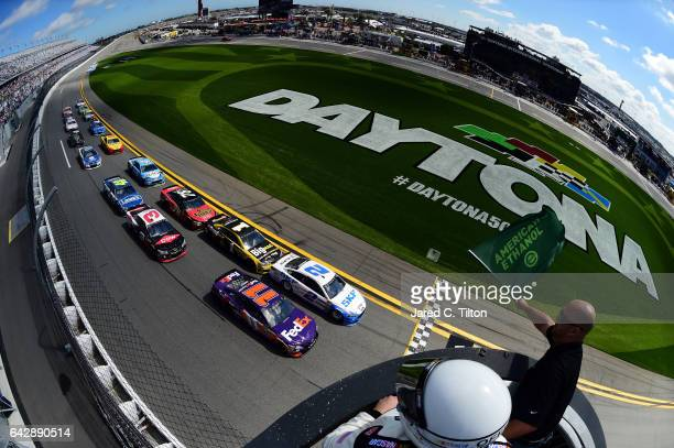 Brad Keselowski driver of the SKF Ford and Denny Hamlin driver of the FedEx Express Toyota lead the field past the green flag to start the weather...