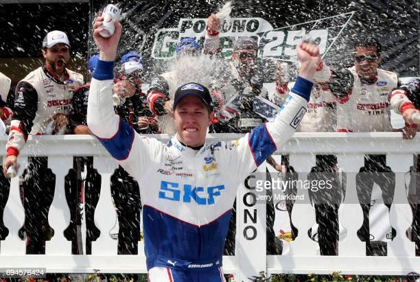 Brad Keselowski driver of the SKF Ford celebrates in Victory Lane after winning the NASCAR XFINITY Series Pocono Green 250 at Pocono Raceway on June...