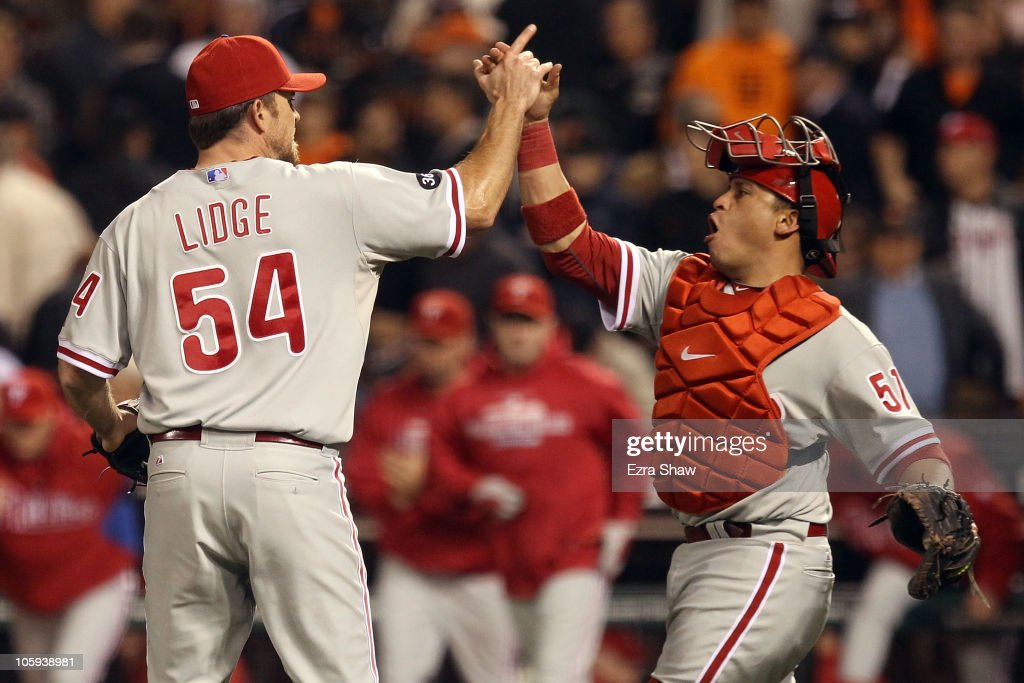 Brad Lidge #54 and Carlos Ruiz #51 of the Philadelphia Phillies celebrate after defeating the San Francisco Giants 4-2 in Game Five of the NLCS during the 2010 MLB Playoffs at AT&T Park on October 21, 2010 in San Francisco, California.