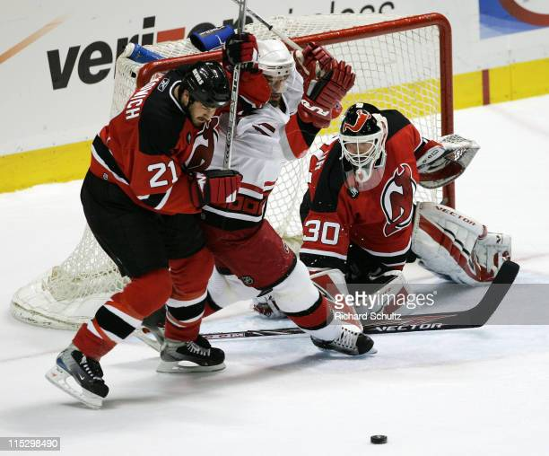 Brad Lukowich of the New Jersey Devils battles Justin Williams of the Carolina Hurricanes for the puck as Devils' goaltender Martin Brodeur protects...