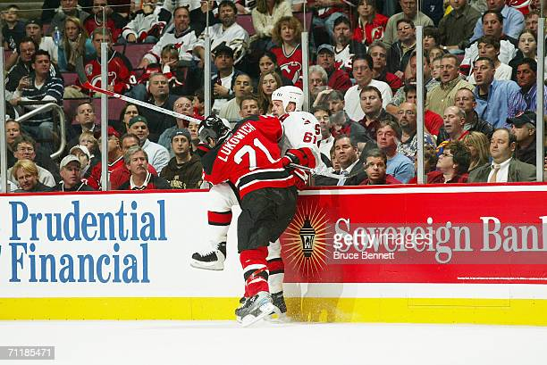Brad Lukowich of the New Jersey Devils checks Cory Stillman of the Carolina Hurricanes along the boards in game three of the Eastern Conference...