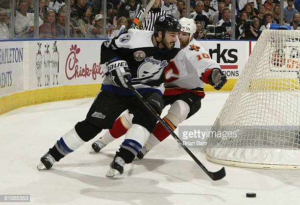 Brad Lukowich of the Tampa Bay Lightning skates with the puck while being pressured by Dave Lowry of the Calgary Flames during Game two of the NHL...