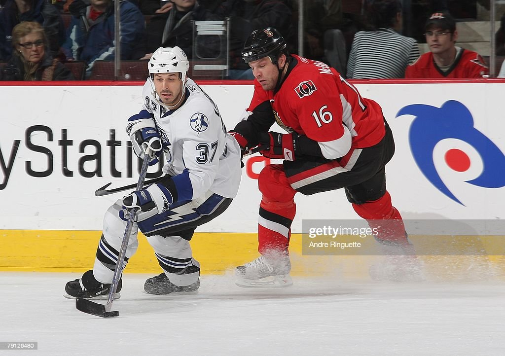 Brad Lukowich #37 of the Tampa Bay Lightning stickhandles the puck away from the pressure of Brian McGrattan #16 of the Ottawa Senators at Scotiabank Place on January 19, 2008 in Ottawa, Ontario, Canada.