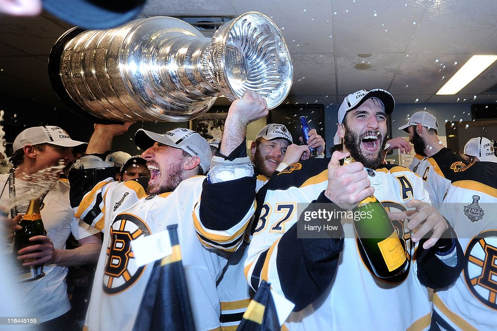Brad Marchand #63 and Patrice Bergeron #37 of the Boston Bruins celebrate with the Stanley Cup in th locker room after Game Seven of the 2011 NHL Stanley Cup Final at Rogers Arena on June 15, 2011 in Vancouver, British Columbia, Canada.