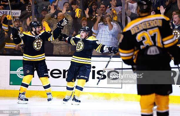 Brad Marchand celebrates with teammate Matt Bartkowski of the Boston Bruins after scoring a goal in the third period against the New York Rangers in...
