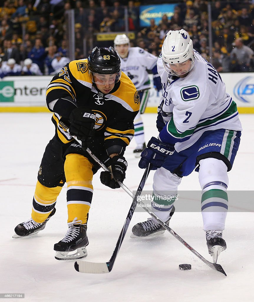 Brad Marchand #63 of the Boston Bruins and Dan Hamhuis #2 of the Vancouver Canucks battle for control of the puck during the third quarter at TD Garden on February 24, 2015 in Boston, Massachusetts. The Canucks defeat the Bruins 2-1.