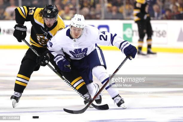 Brad Marchand of the Boston Bruins and Kasperi Kapanen of the Toronto Maple Leafs battle for control of the puck during the second period of Game...