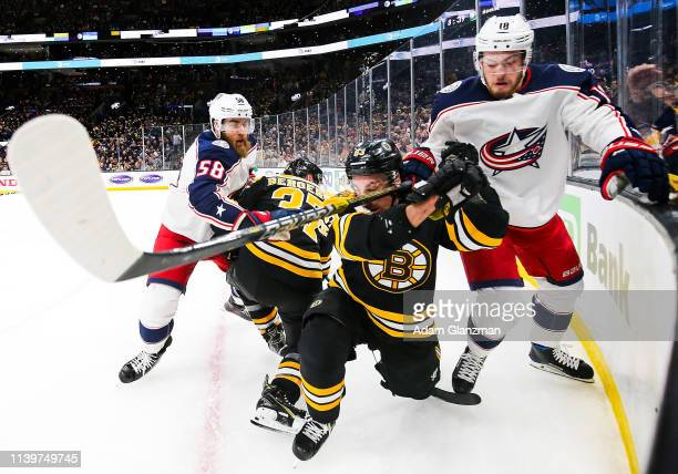 Brad Marchand of the Boston Bruins and Pierre-Luc Dubois of the Columbus Blue Jackets battle for the puck in Game Two of the Eastern Conference...