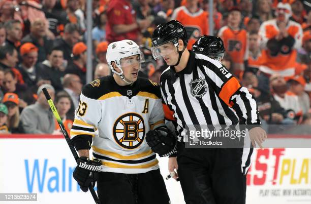 Brad Marchand of the Boston Bruins argues a call with Referee Jake Brenk during a stoppage in play against the Philadelphia Flyers on March 10 2020...