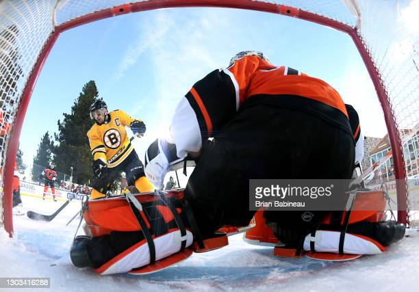 Brad Marchand of the Boston Bruins attempts a shot on goaltender Carter Hart of the Philadelphia Flyers during the first period of the 2021 NHL...
