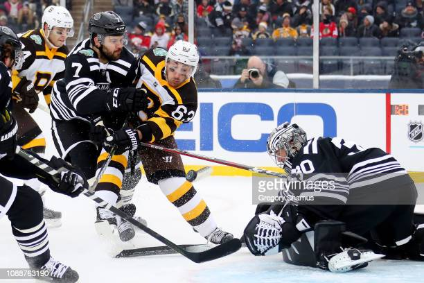 Brad Marchand of the Boston Bruins attempts a shot past Cam Ward of the Chicago Blackhawks as Brent Seabrook defends in the second period during the...