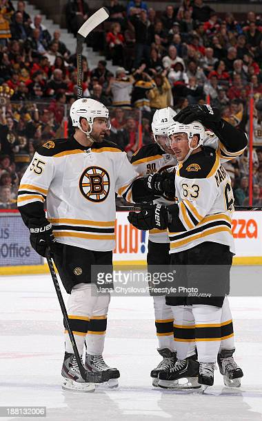 Brad Marchand of the Boston Bruins celebrates his first period goal with teammates Johnny Boychuk and Matt Bartkowski during an NHL game against the...