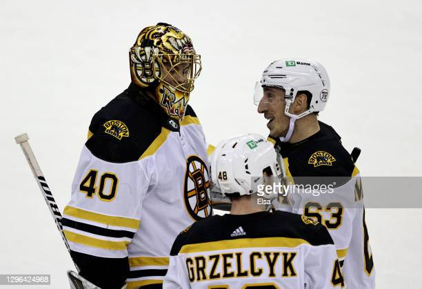 Brad Marchand of the Boston Bruins celebrates his game winning goal with teammates Tuukka Rask and Matt Grzelcyk in the shootout against the New...