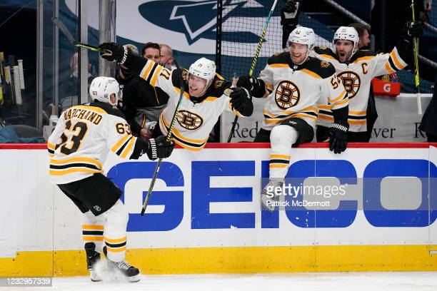 Brad Marchand of the Boston Bruins celebrates with his teammates after scoring the game winning goal against the Washington Capitals in overtime in...
