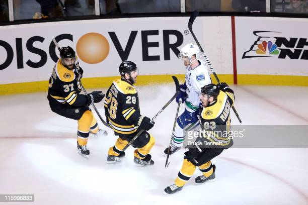 Brad Marchand of the Boston Bruins celebrates with Mark Recchi and Patrice Bergeron after scoring a goal in the first period against Roberto Luongo...