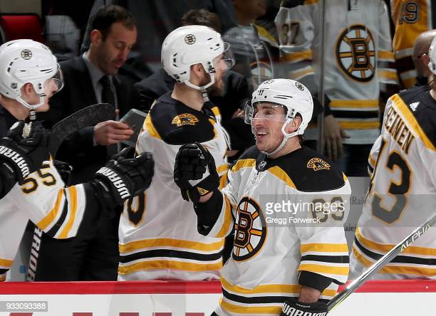 Brad Marchand of the Boston Bruins celebrates with teammates in the bench area during an NHL game against the Carolina Hurricanes on March 13 2018 at...