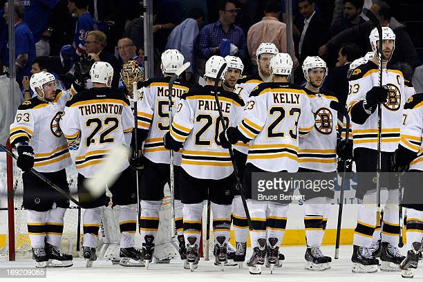 Brad Marchand of the Boston Bruins celebrates with teammates Shawn Thornton and Tuukka Rask after defeating the New York Rangers in Game Three of the...