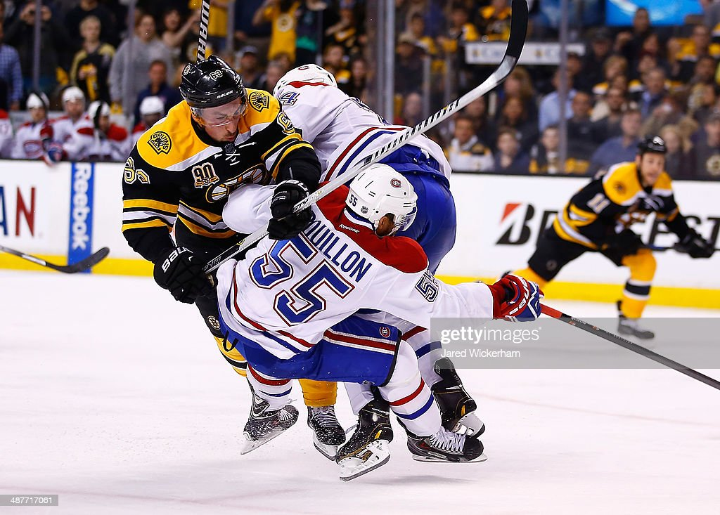Brad Marchand #63 of the Boston Bruins collides with Francis Bouillon #55 and Alexei Emelin #74 of the Montreal Canadiens in the third period in Game One of the Second Round of the 2014 NHL Stanley Cup Playoffs on May 1, 2014 in Boston, Massachusetts.