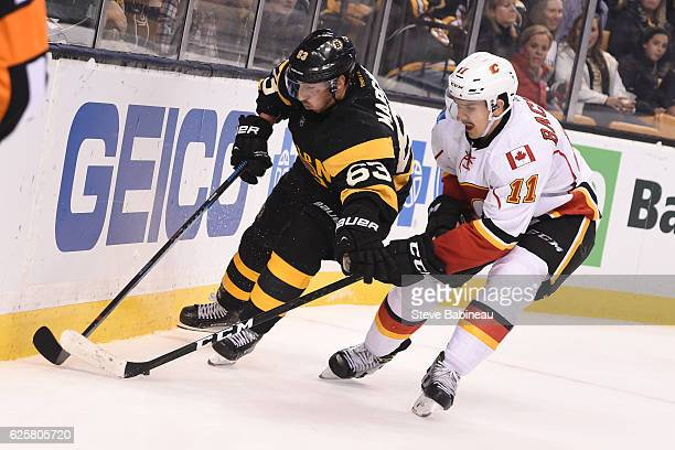 Brad Marchand of the Boston Bruins fight for the puck against Mikael Backlund of the Calgary Flames at the TD Garden on November 25 2016 in Boston...
