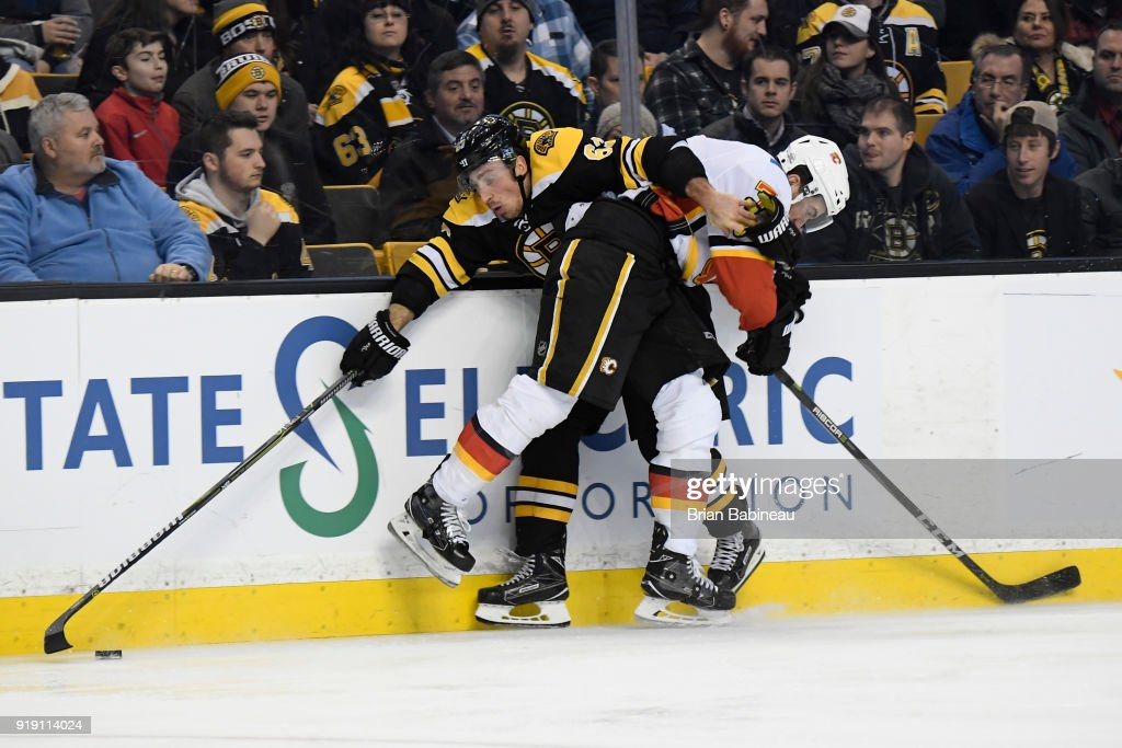 Brad Marchand #63 of the Boston Bruins fights for the puck against the Calgary Flames at the TD Garden on February 13, 2018 in Boston, Massachusetts.