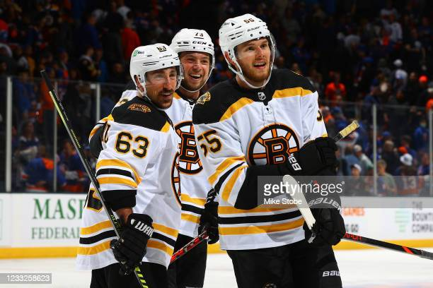 Brad Marchand of the Boston Bruins is congratulated by Charlie McAvoy and Jeremy Lauzon after scoring the game-winning goal in overtime to defeat the...