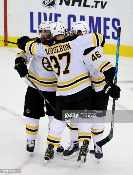 Brad Marchand of the Boston Bruins is congratulated by teammates Patrice Bergeron and David Krejci after he scored a goal the first period against...