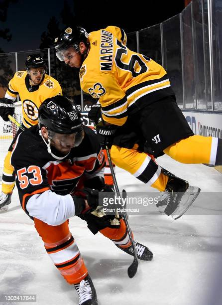 Brad Marchand of the Boston Bruins leaps up above Shayne Gostisbehere of the Philadelphia Flyers during the second period of the 2021 NHL Outdoors...