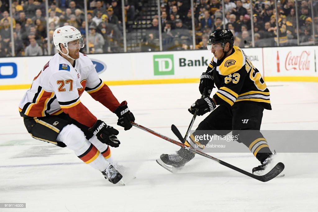 Brad Marchand #63 of the Boston Bruins passes against Dougie Hamilton #27 of the Calgary Flames at the TD Garden on February 13, 2018 in Boston, Massachusetts.