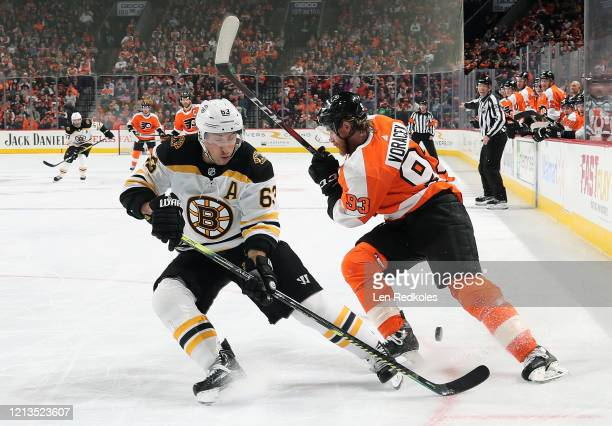 Brad Marchand of the Boston Bruins passes the puck between the legs of Jakub Voracek of the Philadelphia Flyers on March 10 2020 at the Wells Fargo...