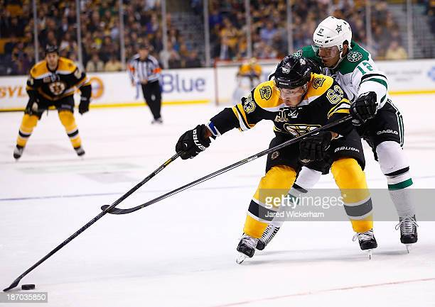 Brad Marchand of the Boston Bruins reaches for a puck in front of Ray Whitney of the Dallas Stars in the first period at TD Garden on November 5 2013...