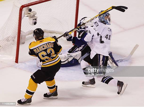 Brad Marchand of the Boston Bruins scores a second period goal past the defense of Martin St Louis and Mike Smith of the Tampa Bay Lightning in Game...