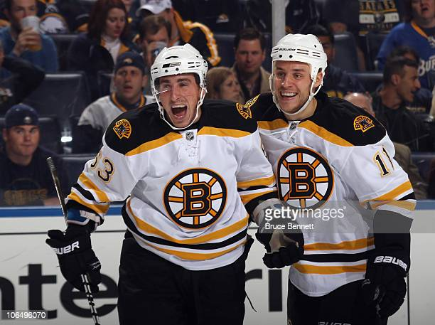 Brad Marchand of the Boston Bruins scores his first NHL goal in the first period against the Buffalo Sabres and is joined by Gregory Campbell at the...