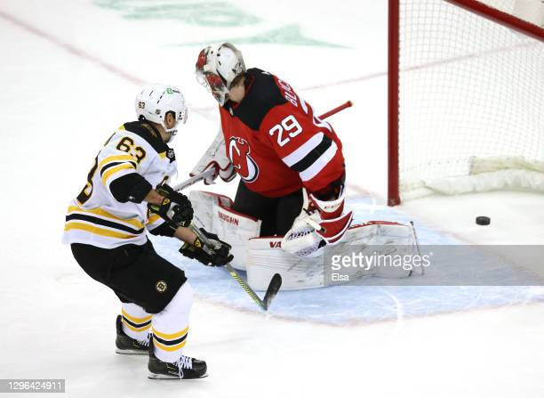 Brad Marchand of the Boston Bruins scores the game winning goal past Mackenzie Blackwood of the New Jersey Devils during the home opening game at...
