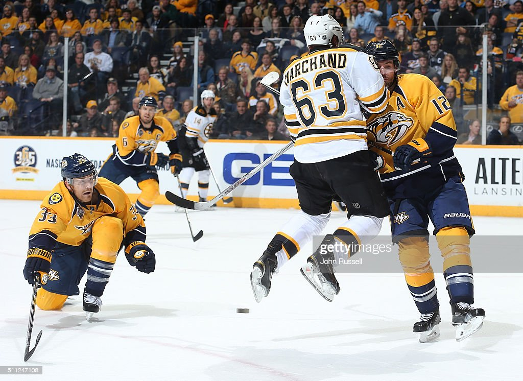 Brad Marchand #63 of the Boston Bruins screens a shot against Colin Wilson #33 and Mike Fisher #12 of the Nashville Predators during an NHL game at Bridgestone Arena on February 18, 2016 in Nashville, Tennessee.