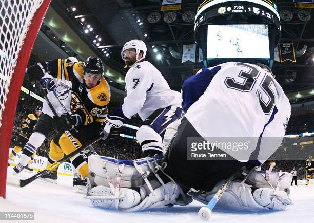 Brad Marchand of the Boston Bruins shoots against the defense of Brett Clark and Dwayne Roloson of the Tampa Bay Lightning in Game Two of the Eastern...