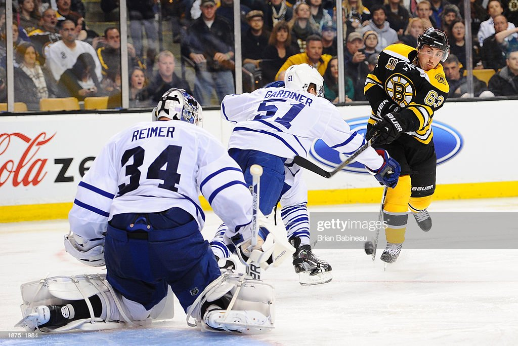 Brad Marchand #63 of the Boston Bruins shoots the puck against Jake Gardiner #51 and James Reimer #34 of the Toronto Maple Leafs at the TD Garden on November 9, 2013 in Boston, Massachusetts.